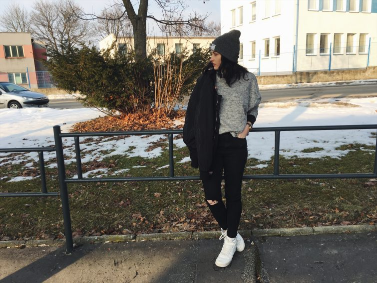 Simona v roztrhaných džínech, s bomber bundou a bílými Nike.