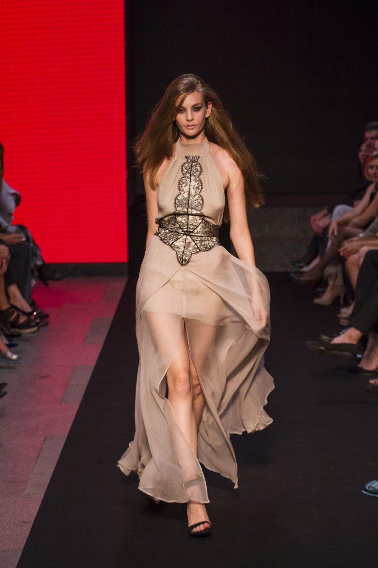 Model společenských šatů na přehlídkovém mole